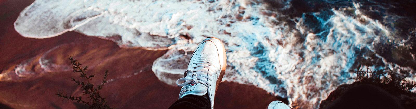 Feet dangling over a cliff overlooking a beach