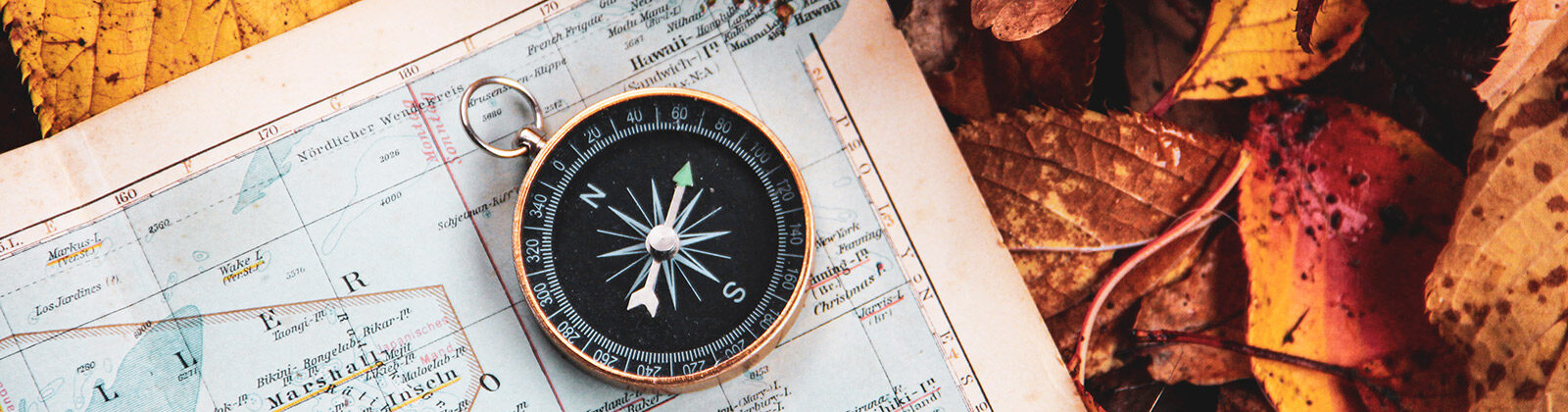 Compass laying on a map with fall leaves in the background