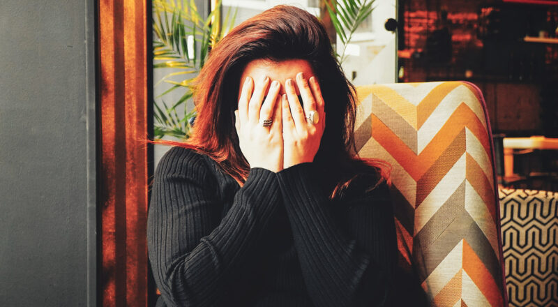 Woman sitting on a couch with her hands covering her face