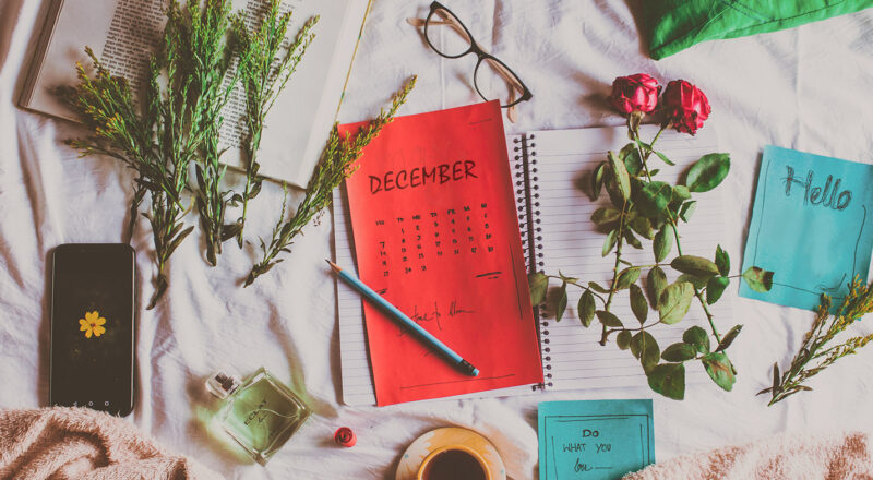Miscellaneous items spread out including a calendar for December and a notebook for year end review and reflection
