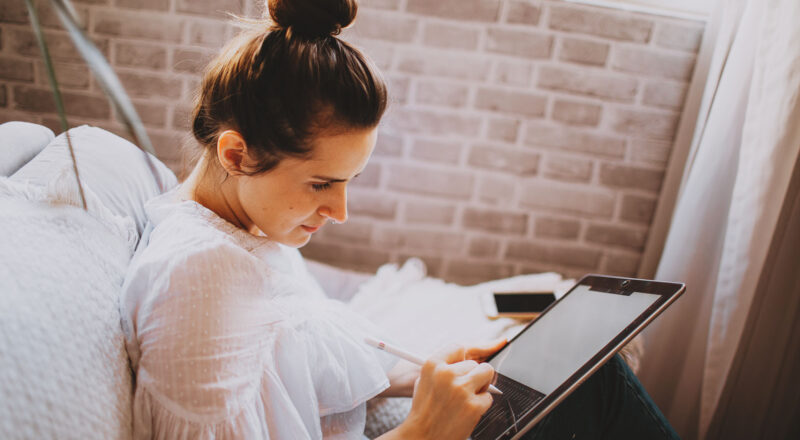 Woman sitting on couch sketching on her digital tablet