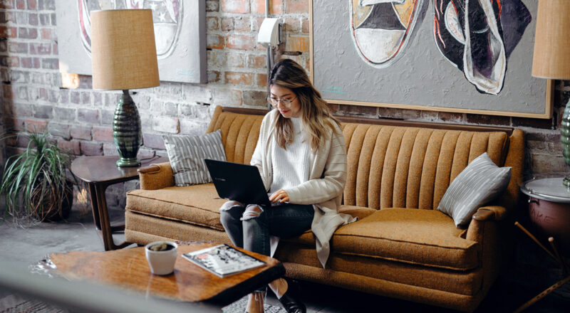 Woman sitting on couch typing on her laptop