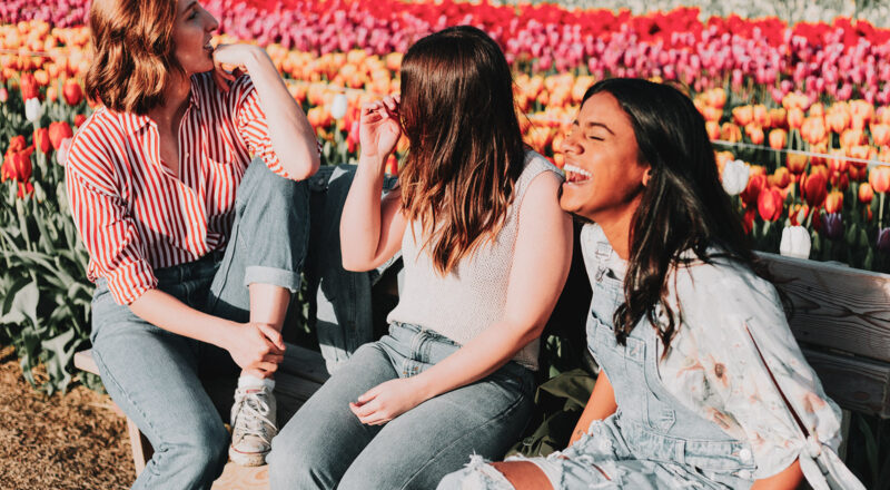 Three women talking and laughing. They are sitting on a bench in front of a tulip field.