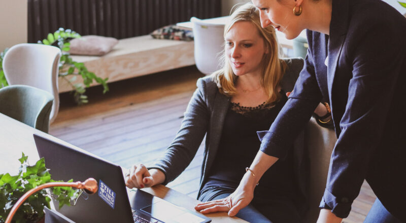 Two women entrepreneurs, one sitting and one standing leaning with her hands on desk, both looking at a laptop screen