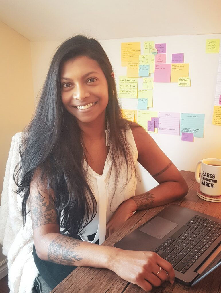 Ruha is wearing a white blouse and long hair. She is smiling, sitting at a desk with a laptop and a mug that reads 'babes supporting babes'. The wall behind her is covered in colourful post-it notes.